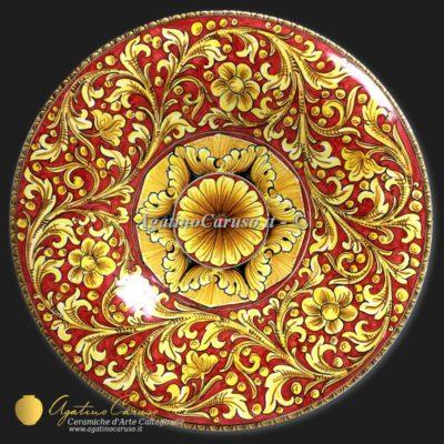 Piatto in maiolica Siciliana delle Ceramiche Artistiche di Agatino Caruso. Dipinto con ornato in giallo ocra e fondo rosso intenso