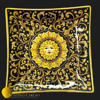 Piatto ornamentale da muro in ceramica artistica dipinto a mano da Agatino Caruso a Caltagirone. Decoro ornato fondo nero lucido e sole centrale